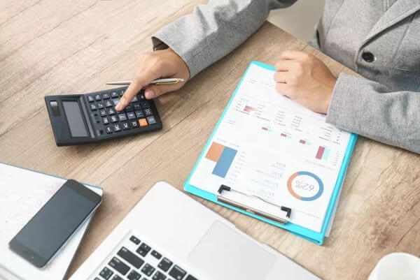 Mulher usando a calculadora em uma mesa, onde também há uma prancheta, em cuja folha há alguns números e gráficos. Na mesa, também há um celular e um notebook.
