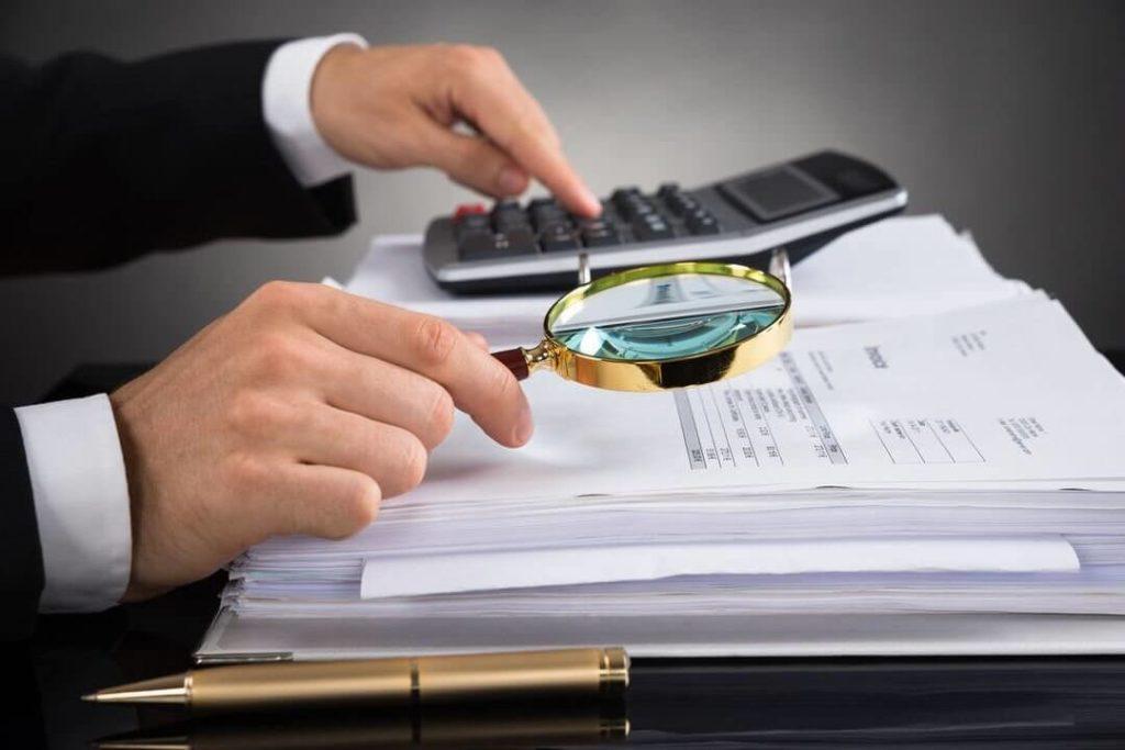 Homem com lupa olhando as contas da empresa
