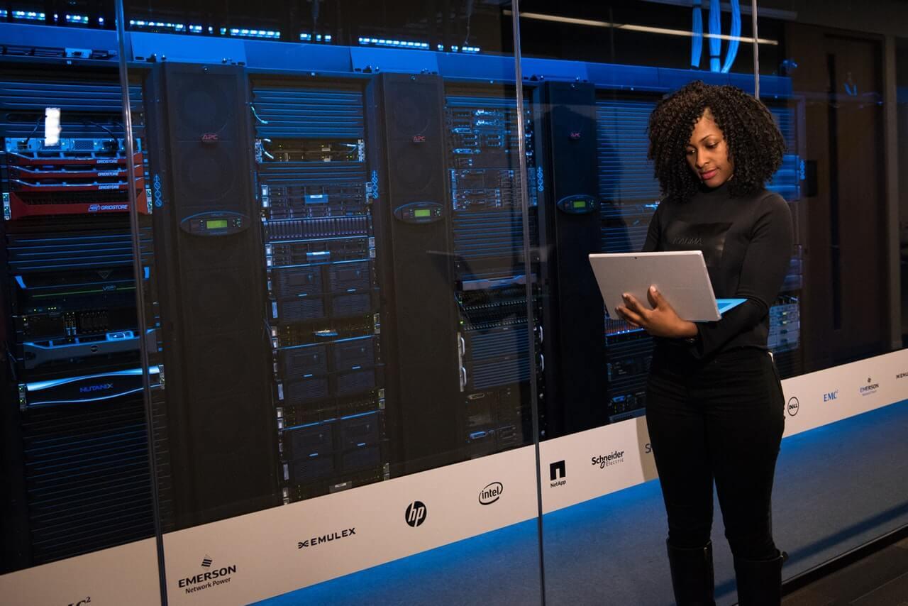 Mulher em pé em frente a uma sala de tecnologia