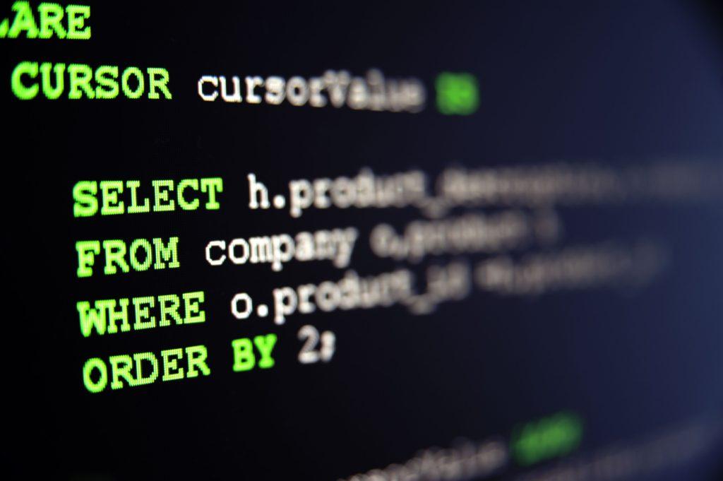 A imagem mostra os códigos de computador, em um fundo preto, com escritas em verde