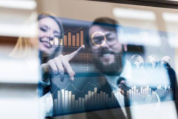 Duas pessoas, vistas pelo reflexo de um vidro, apontam para a tela de um computador, o qual exibe uma série de gráficos, indicando a presença de um controle financeiro exemplar.