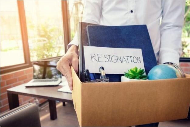 Pessoa segurando caixa com a mensagem de demissão